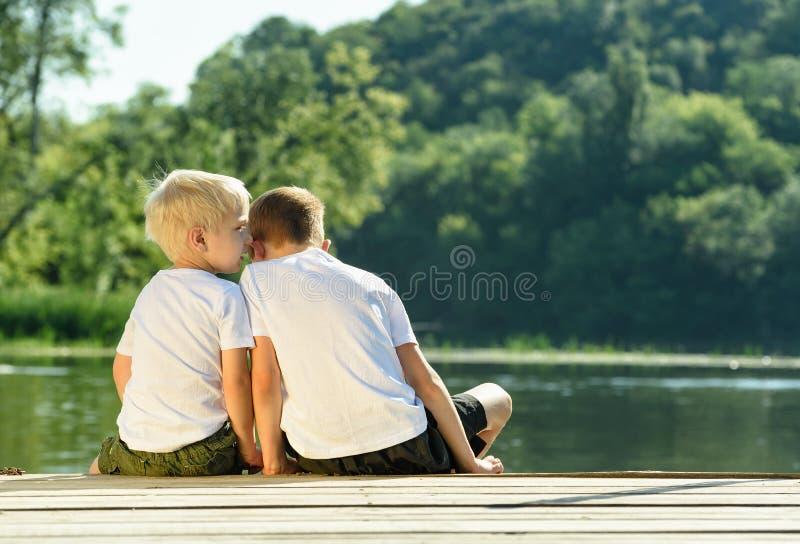 Chłopiec szepcze inny ucho, siedzi na banku rzeka obrazy stock