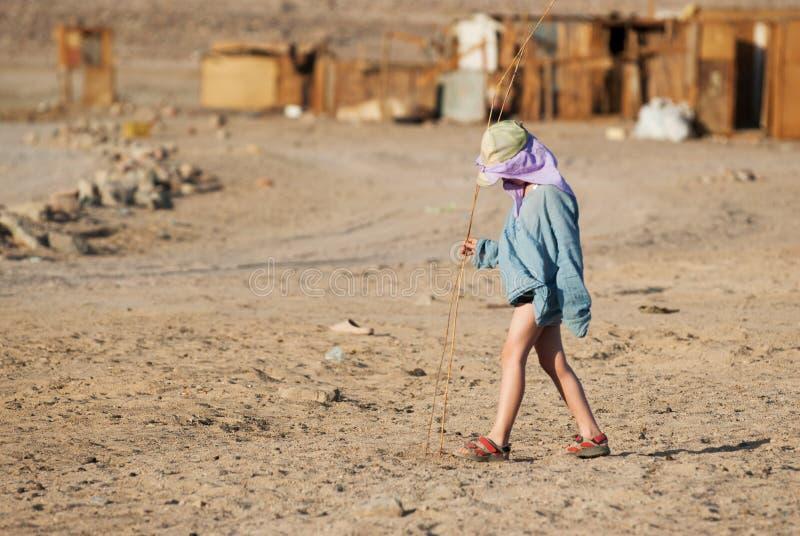 Chłopiec turysta chodzi w Beduińskiej wiosce z trzcin sprigs w jego rękach zdjęcie royalty free