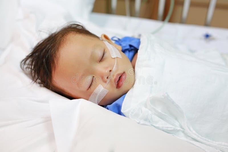 Chłopiec wiek o 1 roczniaka dosypianiu na cierpliwym łóżku z dostawać tlen przez nosowych prongs gwarantować tlenowego przepojeni obraz stock
