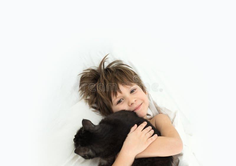 Chłopiec z kotem kłama w łóżku na białych bedclothes zdjęcia royalty free