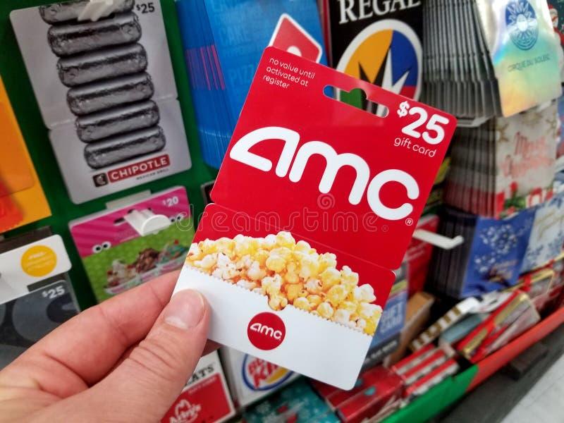 Chèque-cadeau d'AMC dans une main photographie stock