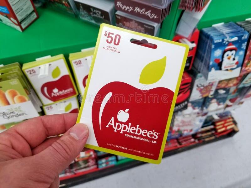 Chèque-cadeau d'Applebees dans une main photographie stock