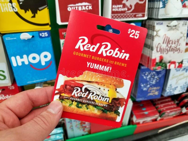 Chèque-cadeau rouge de Robin dans une main images libres de droits