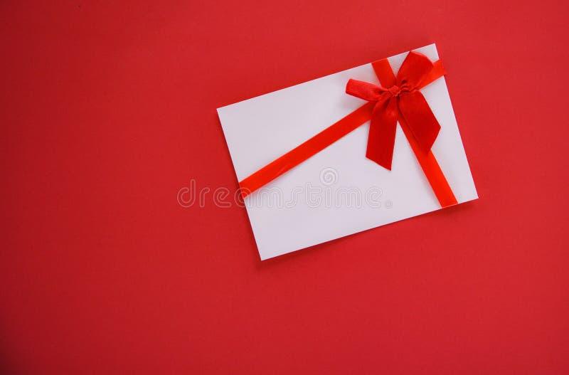 Chèque-cadeau sur le fond rouge avec le bon de cadeau rouge d'arc de ruban sur l'espace rouge de copie de vue supérieure de fond photos stock