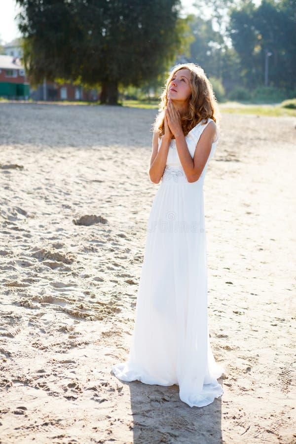 Chère jeune mariée de prière de fille dans une robe blanche sur l'extérieur ensoleillé photo stock