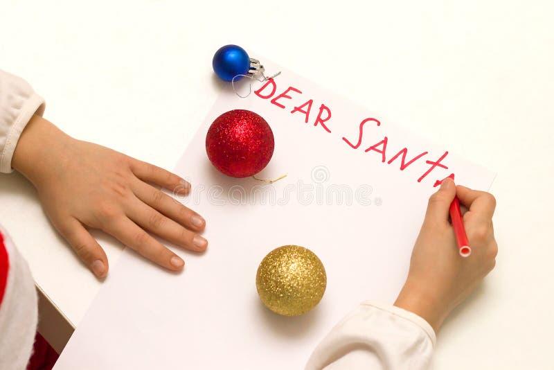 Chère Santa - souhaitez la carte écrite par l'enfant à Santa Claus à Noël Le ` s d'enfant remet la lettre d'écriture avec un pens image libre de droits