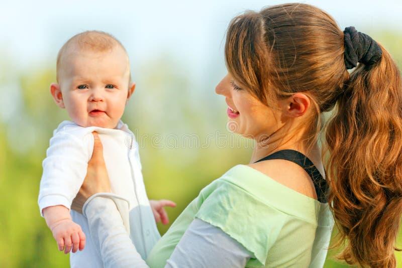 Chéri étonnée par fixation de sourire de mère dans des mains photo libre de droits