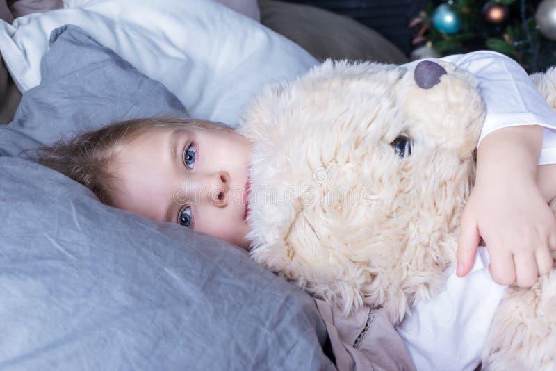 Chéri étreignant un ours de nounours Une petite fille avec les cheveux blonds dans le lit se trouve avec ses yeux ouverts photos stock