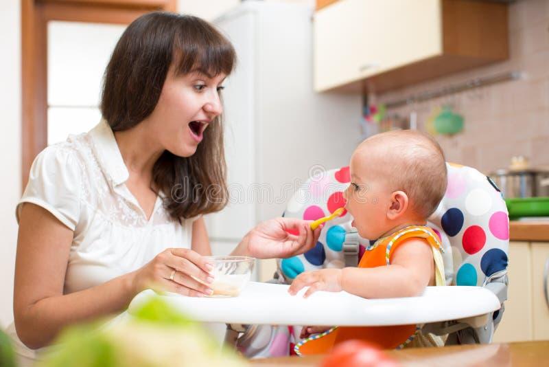 Chéri alimentante de mère avec la cuillère photo stock