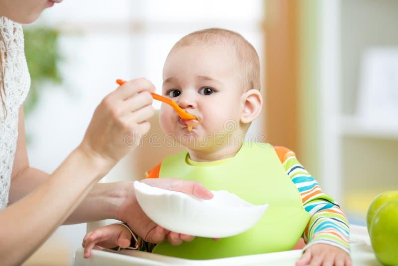 Chéri alimentante de mère avec la cuillère photos libres de droits