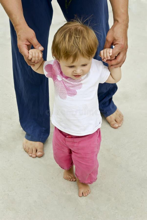 Chéri apprenant à marcher avec un adulte photo libre de droits
