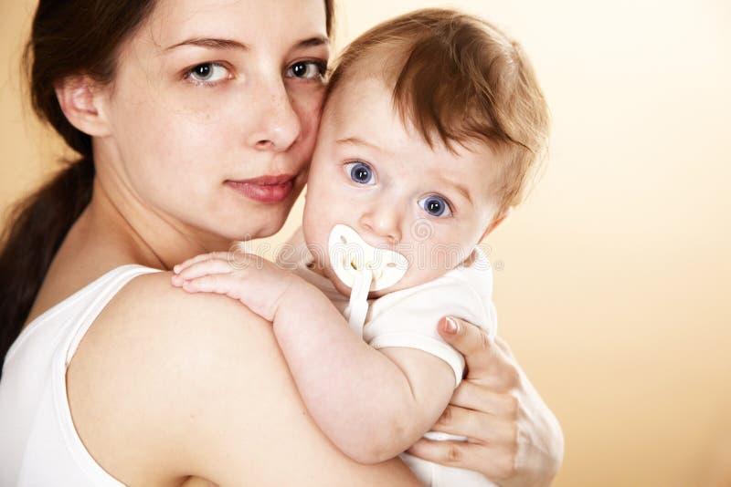 Chéri avec le pacificateur dans le bras de mère images stock