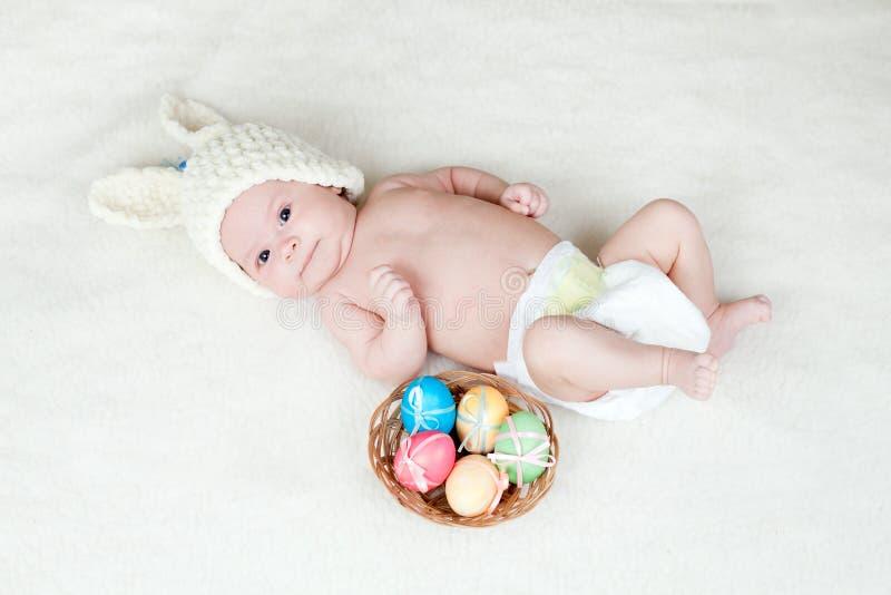 Chéri dans le capuchon de lapin de Pâques avec des oeufs dans le panier photographie stock
