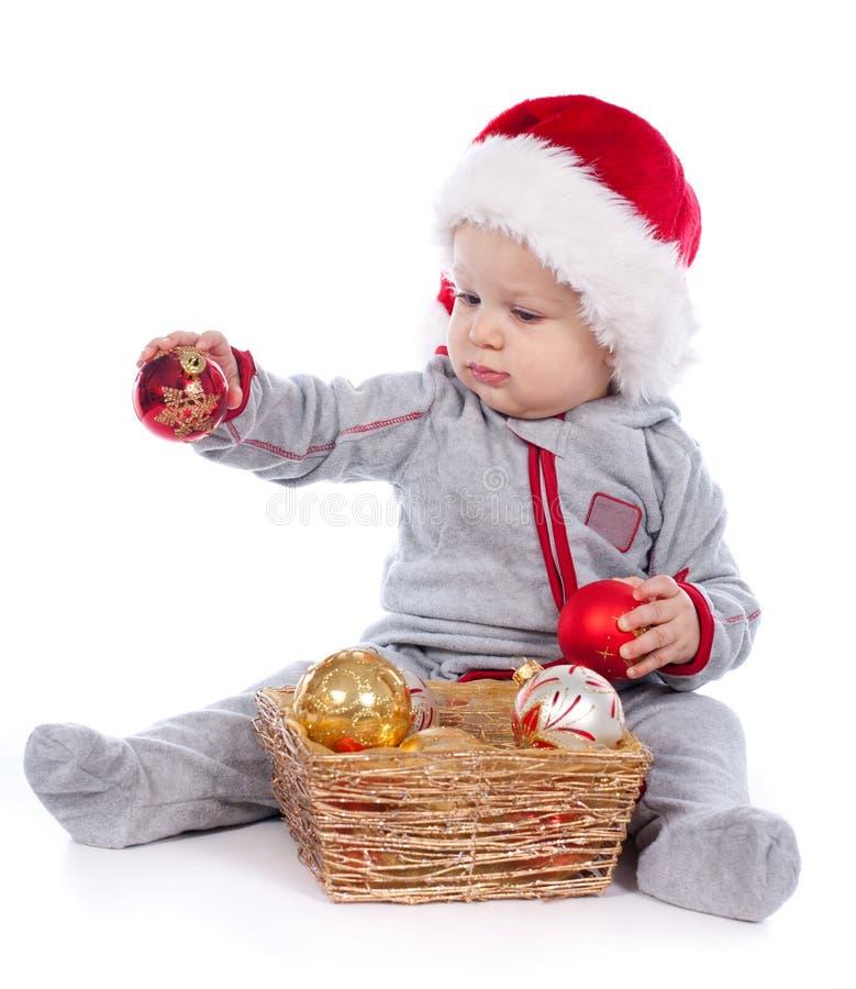 Chéri dans le chapeau de Santa jouant avec des billes de Noël photos libres de droits