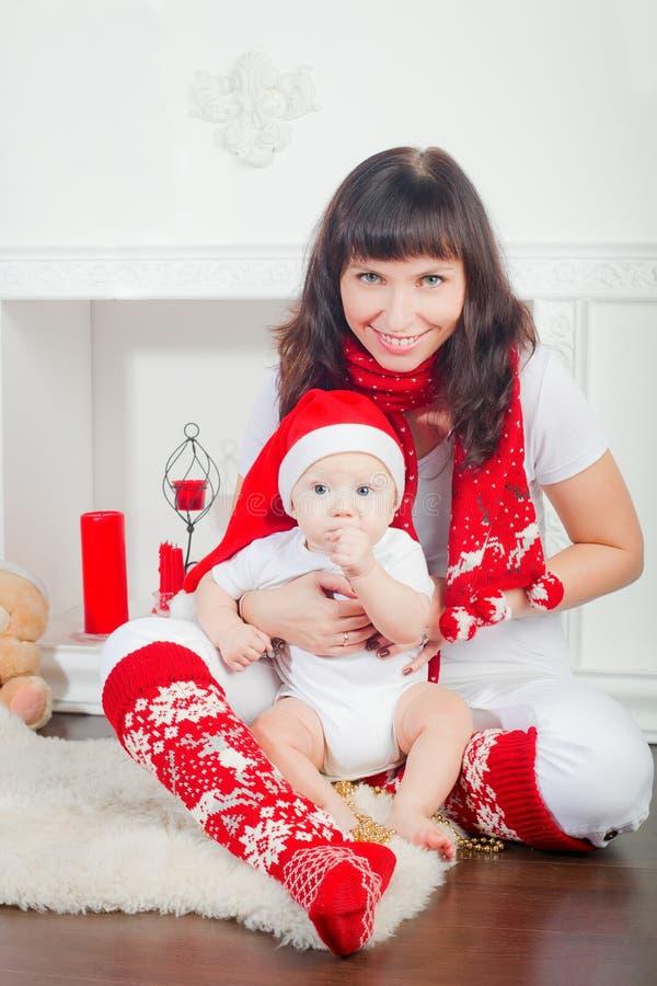 Chéri dans le chapeau et sa mère de Santa photos stock