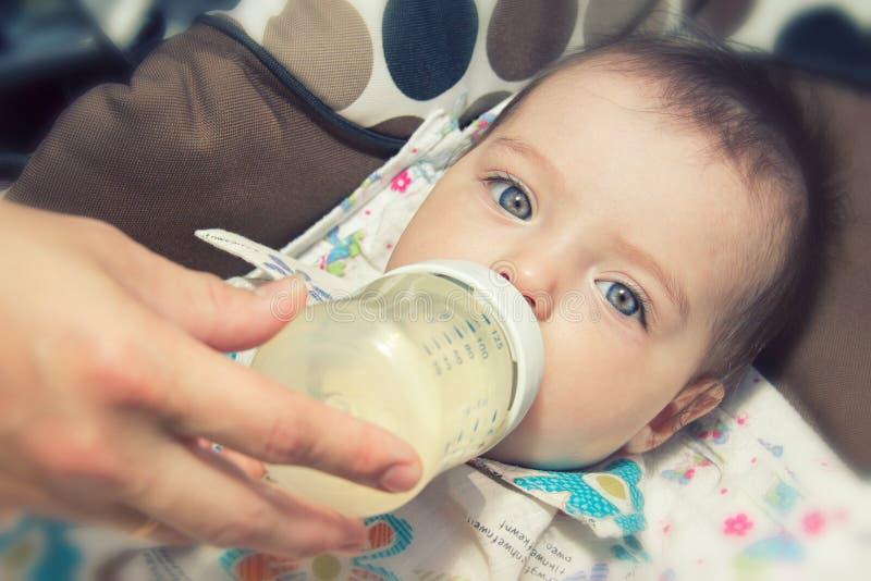 Chéri de sept mois adorable mangeant de la bouteille photos stock