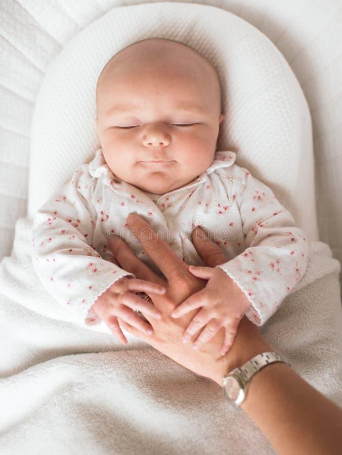 Chéri dormant et retenant la main du parent image stock
