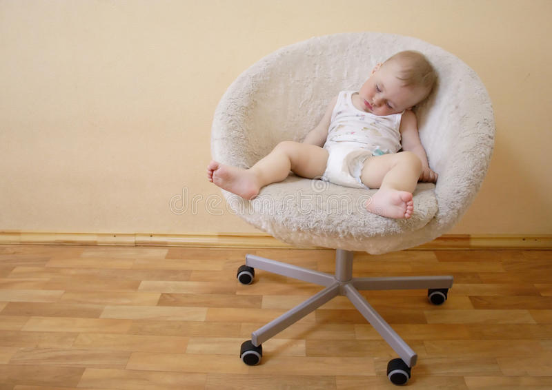 Chéri dormant sur la présidence photographie stock libre de droits
