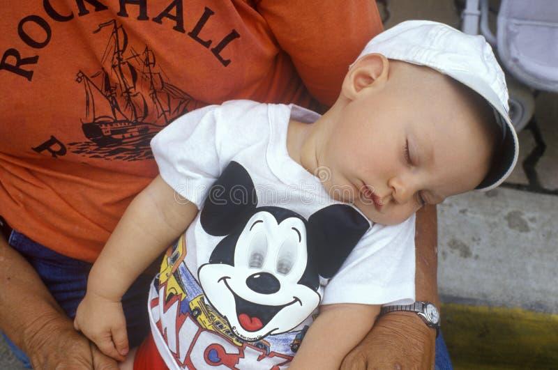 Chéri en sommeil dans des bras de mères à la 4ème du défilé de juillet photos libres de droits