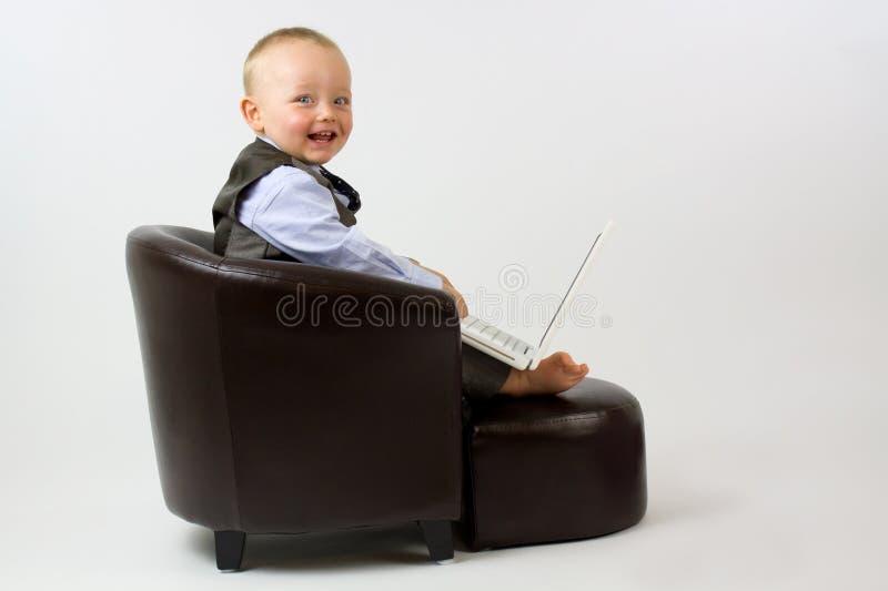 Chéri heureuse dans la présidence en cuir avec l'ordinateur portatif image stock
