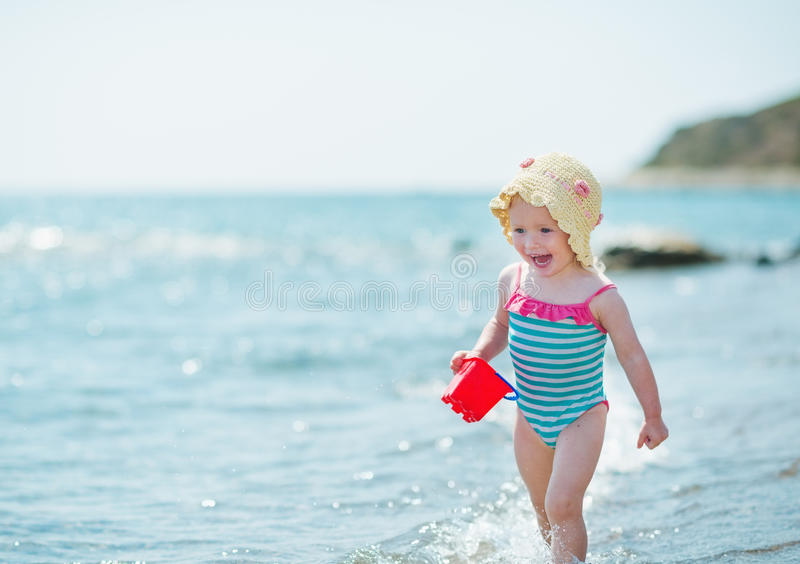 Chéri heureuse exécutant le long du bord de mer photographie stock