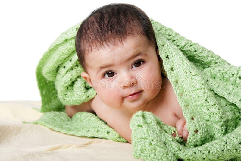 Chéri heureuse mignonne entre les couvertures vertes photo libre de droits