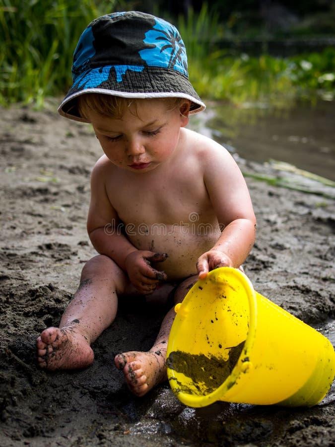Chéri jouant sur la plage photo stock