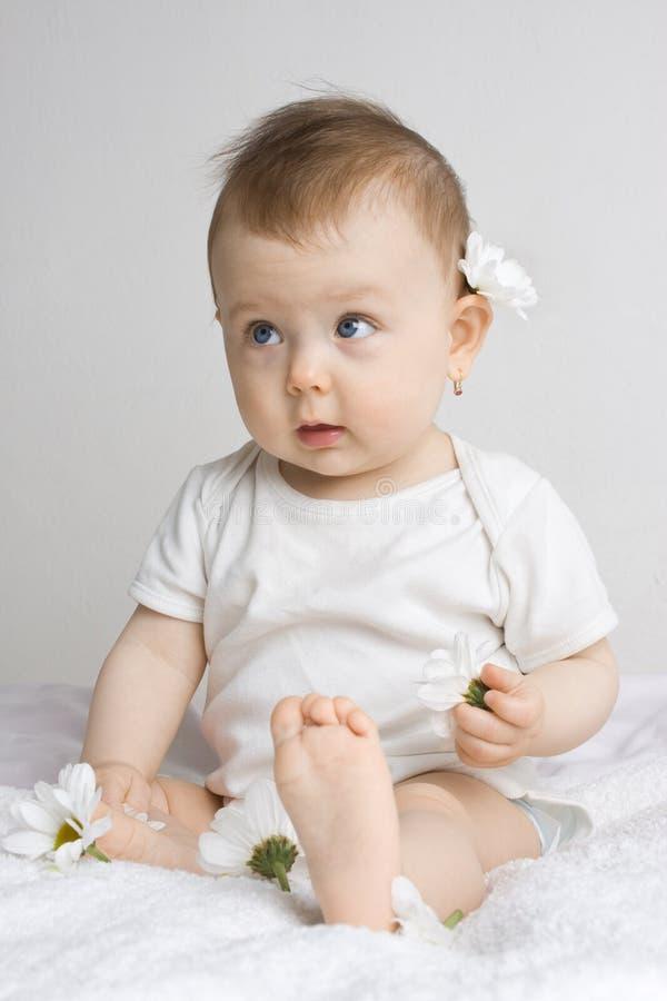 Chéri mignonne jouant avec des fleurs photos libres de droits