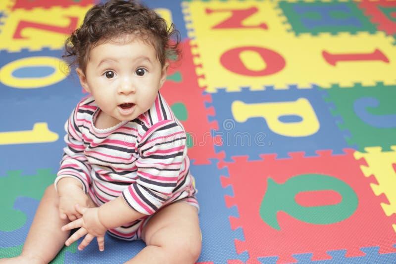 Chéri mignonne sur un couvre-tapis de pièce image libre de droits