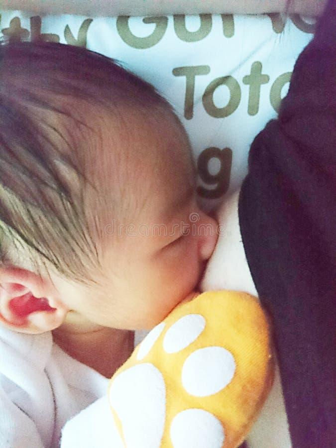 Chéri nouveau-née allaitant au sein image libre de droits