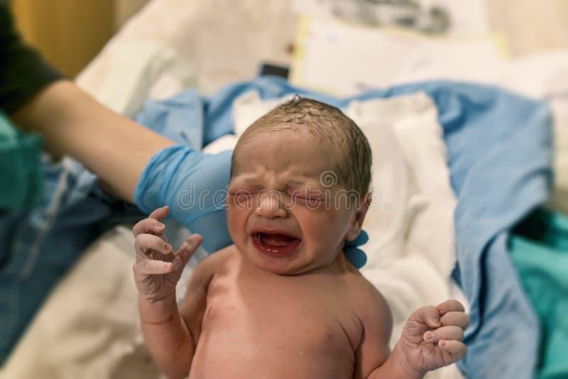 Chéri nouveau-née bébé sans vêtements et pleurer dessus Infirmière tenant le bébé photographie stock libre de droits
