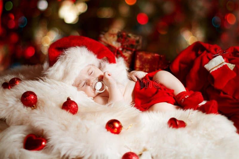 Chéri nouveau-née de Noël dormant dans le chapeau de Santa photo libre de droits