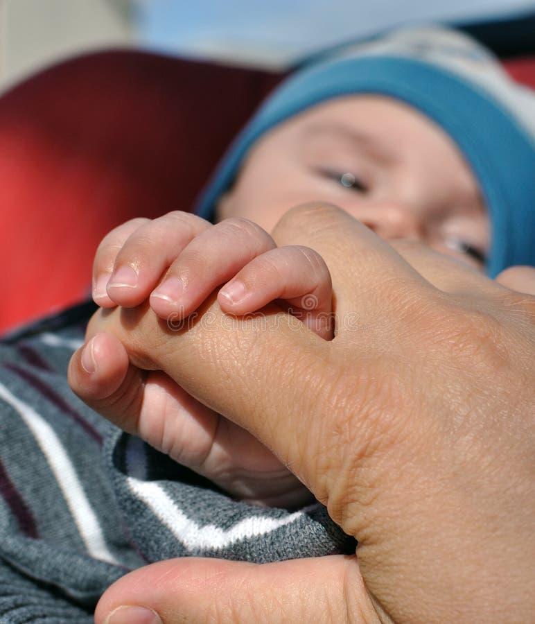 Chéri retenant le doigt de mère images stock