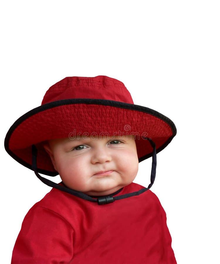Chéri sceptique dans le chapeau rouge. image libre de droits