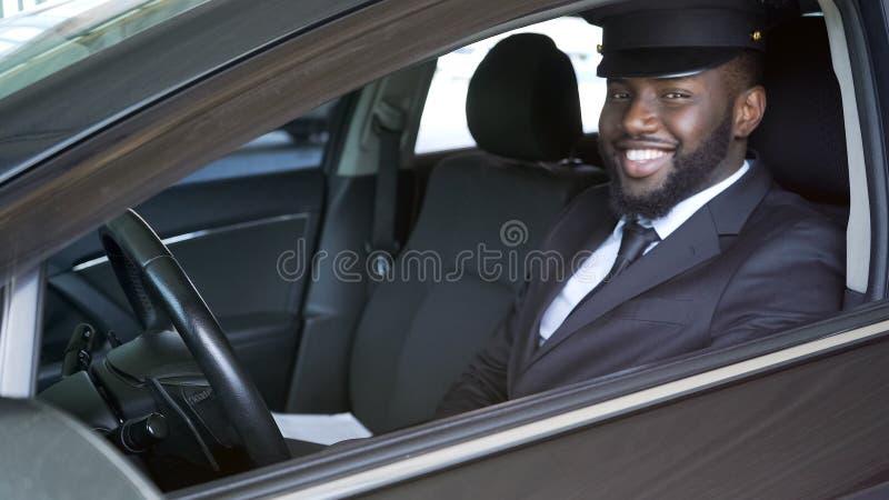 Chófer afroamericano feliz que mira en la cámara, transferencia de lujo, servicio foto de archivo