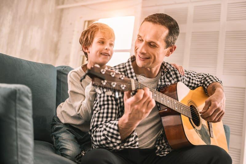 Chętna młoda chłopiec pyta jego ojca uczyć on everything o muzyce obraz royalty free