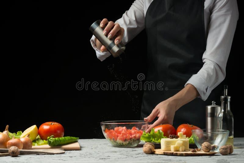 Chłodni jedzenie przygotowywa w proces jarskiej sałatce szef kuchni ręką w domowej kuchni Ciemnego czerni tło z teksta terenem dl zdjęcie royalty free