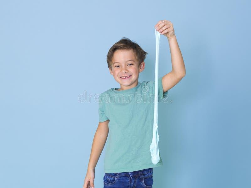 Chłodno, ładna chłopiec, bawić się z domowej roboty śluzowacieje przed błękitnym tłem i ma mnóstwo zabawę obraz royalty free
