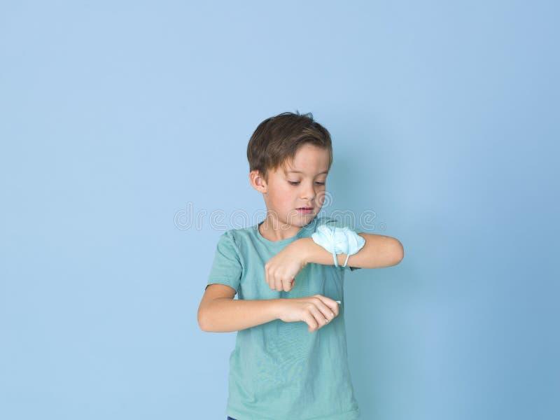 Chłodno, ładna chłopiec, bawić się z domowej roboty śluzowacieje przed błękitnym tłem i ma mnóstwo zabawę obrazy stock