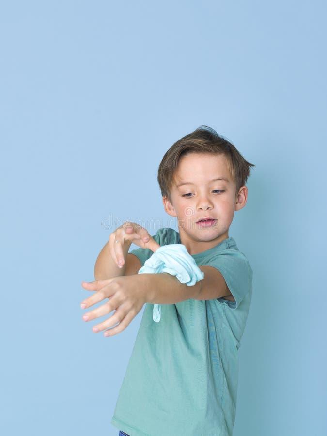 Chłodno, ładna chłopiec, bawić się z domowej roboty śluzowacieje przed błękitnym tłem i ma mnóstwo zabawę zdjęcia stock