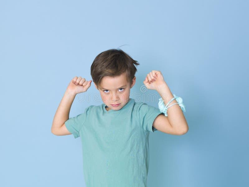 Chłodno, ładna chłopiec, bawić się z domowej roboty śluzowacieje przed błękitnym tłem i ma mnóstwo zabawę zdjęcie stock