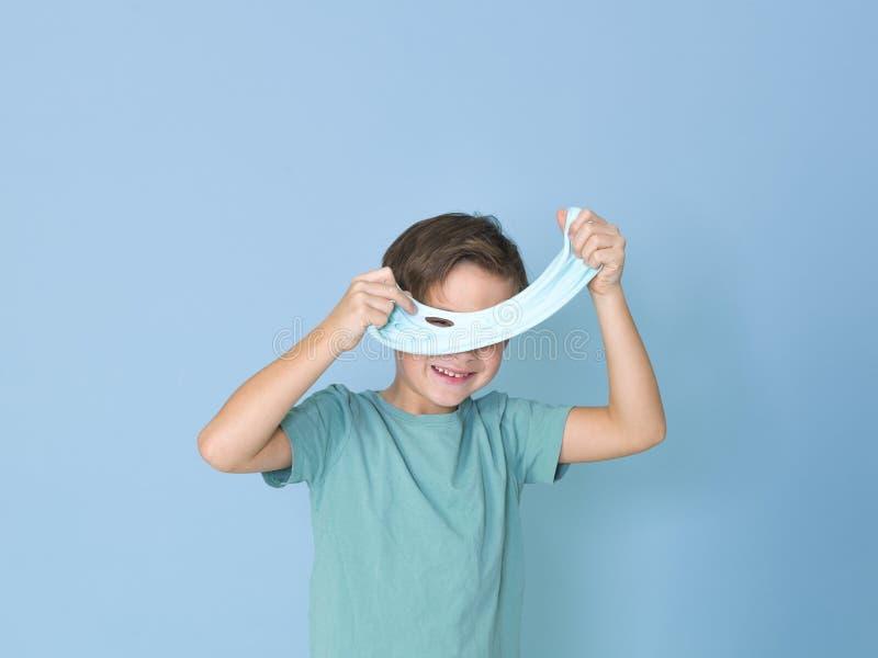 Chłodno, ładna chłopiec, bawić się z domowej roboty śluzowacieje przed błękitnym tłem i ma mnóstwo zabawę zdjęcie royalty free