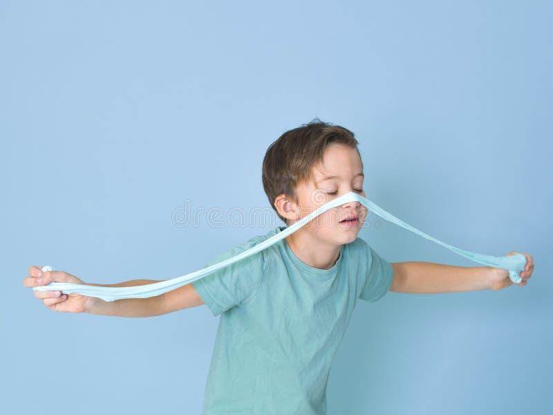 Chłodno, ładna chłopiec, bawić się z domowej roboty śluzowacieje przed błękitnym tłem i ma mnóstwo zabawę fotografia stock