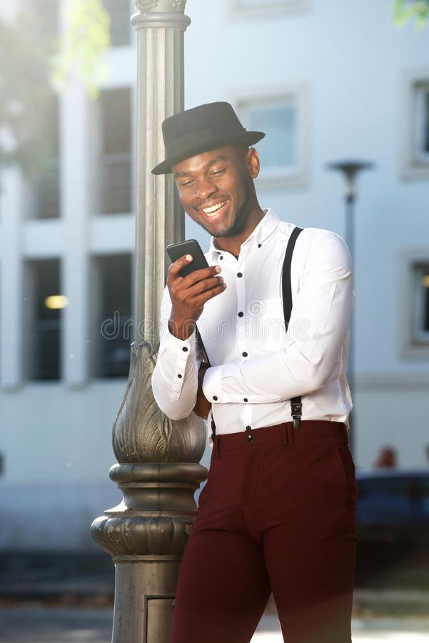 Chłodno amerykanin afrykańskiego pochodzenia mody męski model pozuje z kapeluszem i telefonem komórkowym w mieście zdjęcia royalty free