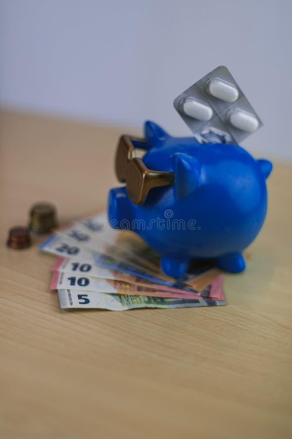 Chłodno błękitny prosiątko bank z złotymi szkłami z pigułkami i euro coi fotografia stock