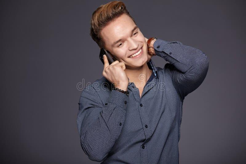 Chłodno biznesowy mężczyzna opowiada na telefonie komórkowym Popielaty tło fotografia stock