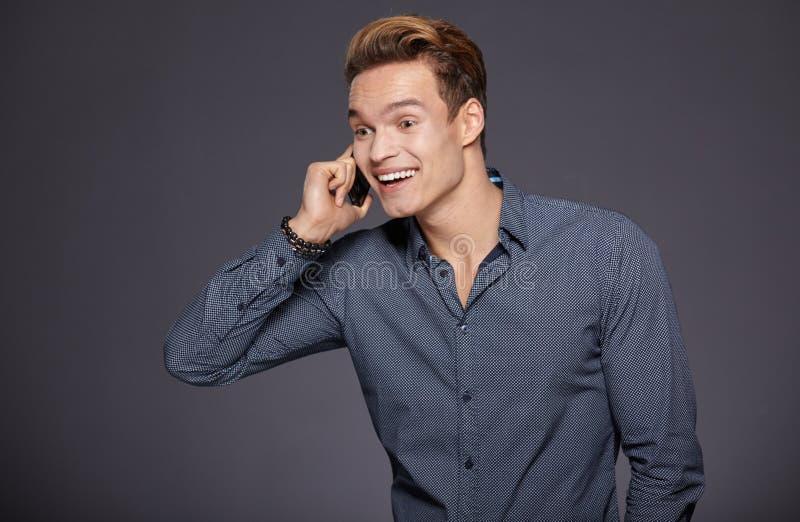 Chłodno biznesowy mężczyzna opowiada na telefonie komórkowym Popielaty tło zdjęcia stock