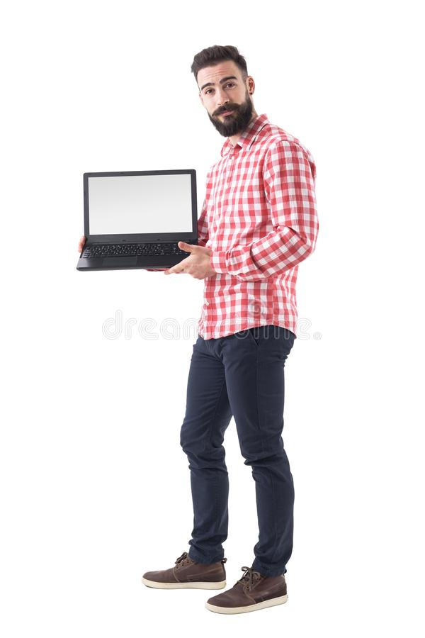 Chłodno brodaty modnisia facet w mądrze przypadkowych ubraniach pokazuje pustego laptop monitoruje obraz stock