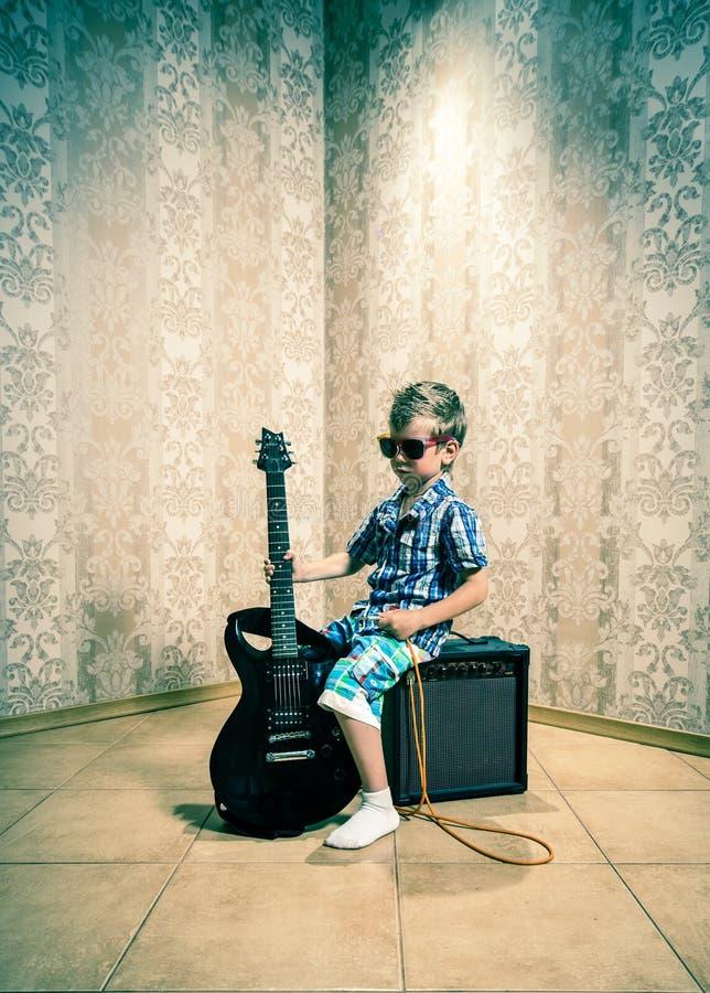 Chłodno chłopiec pozuje z gitarą elektryczną zdjęcia stock
