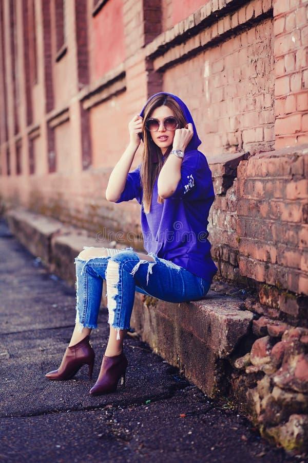 Chłodno dziewczyna jest ubranym cajgi i okulary przeciwsłonecznych obraz royalty free
